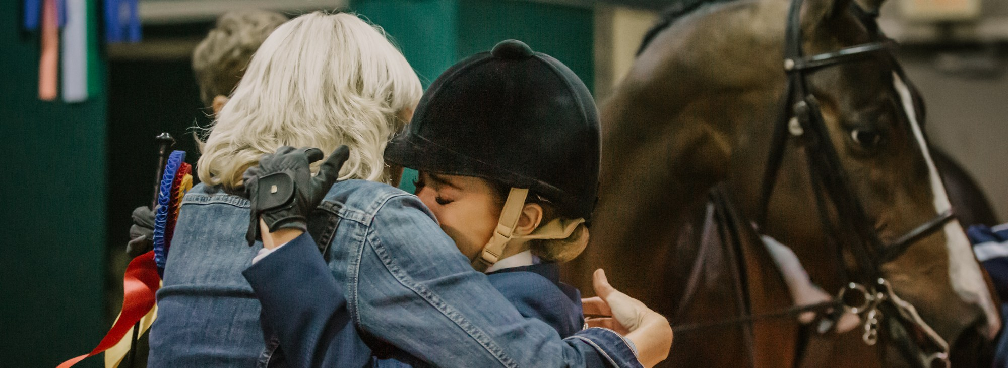 Two people hugging with Morgan horse begin them